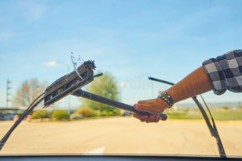 Mujer que limpia el parabrisas del coche con el enjugador al aire libre foto de archivo libre de regalías