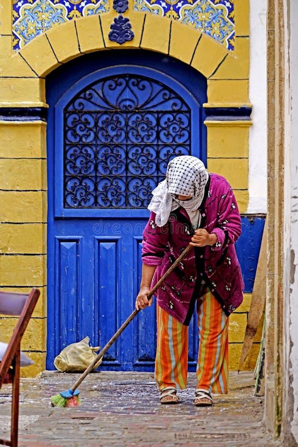 Mujer que limpia en el Medina de Essaouira imagen de archivo