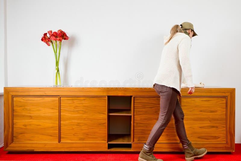 Mujer que limpia la cómoda de madera marrón vacía con tres flores en el coche rojo carped fotografía de archivo