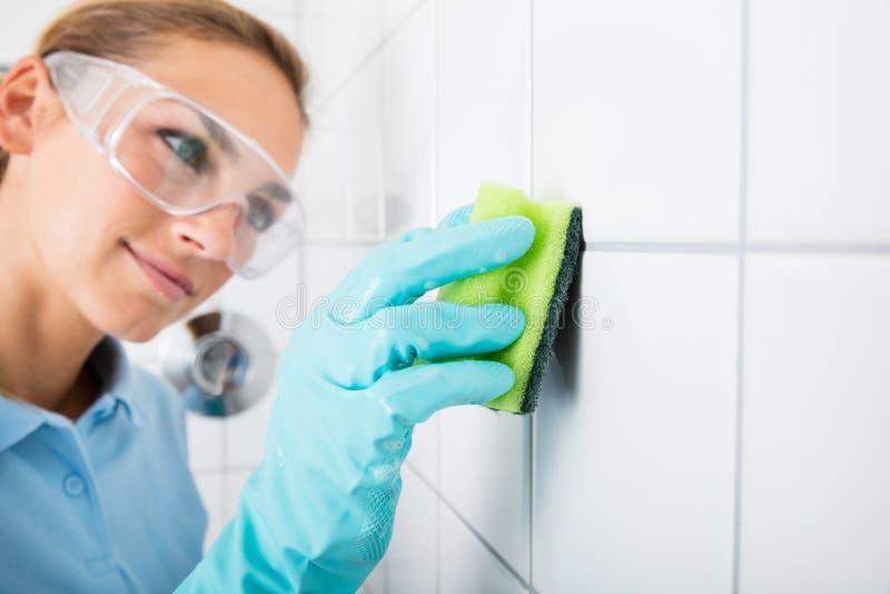 Mujer que limpia la teja blanca de la pared foto de archivo libre de regalías