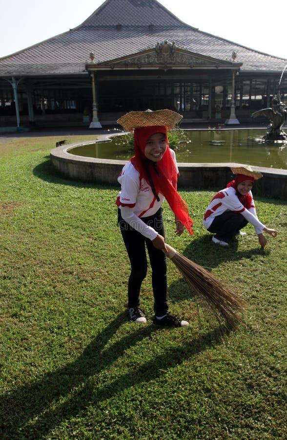 Mujer que limpia la yarda alrededor del templo Mangkunegaran Java central Indonesia foto de archivo