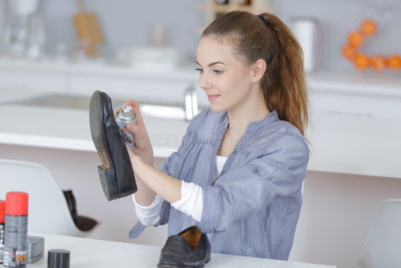 Mujer que limpia los zapatos imagen de archivo libre de regalías