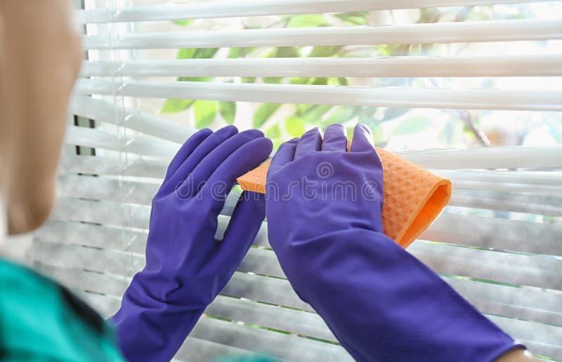 Mujer que limpia persianas de ventana con el trapo dentro Antes y despu?s de la limpieza imagenes de archivo