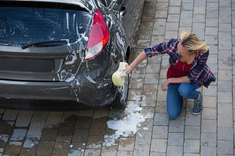 Mujer que limpia su coche con la esponja fotografía de archivo libre de regalías