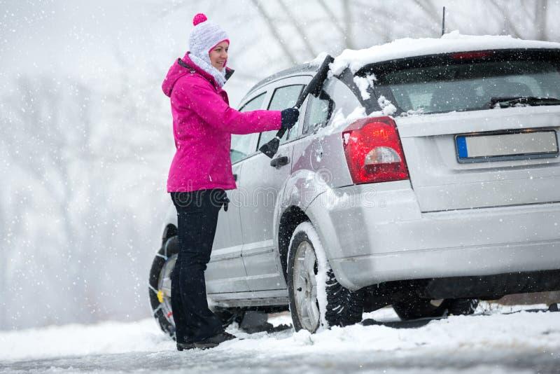 Mujer que limpia su coche de nieve foto de archivo