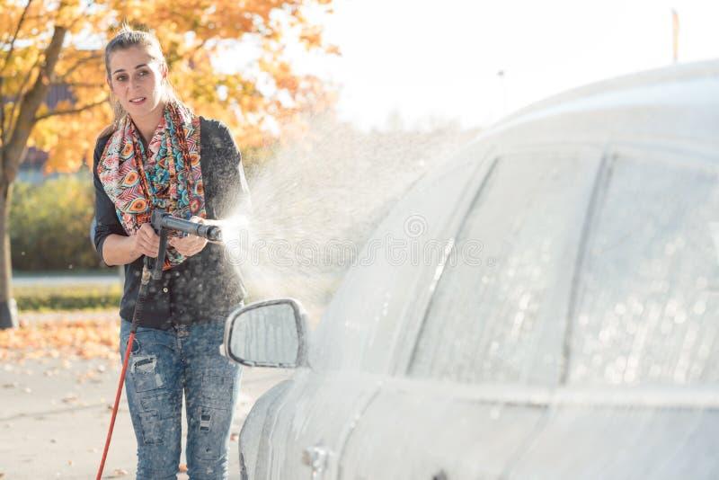 Mujer que limpia su vehículo en túnel de lavado del autoservicio imagenes de archivo