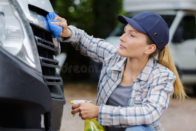 Mujer que limpia un coche imagenes de archivo