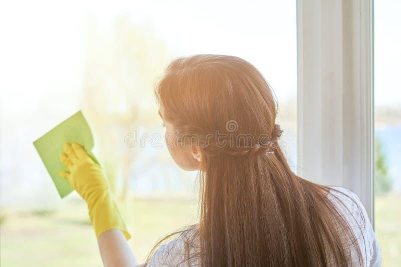 Mujer que limpia una ventana fotos de archivo libres de regalías