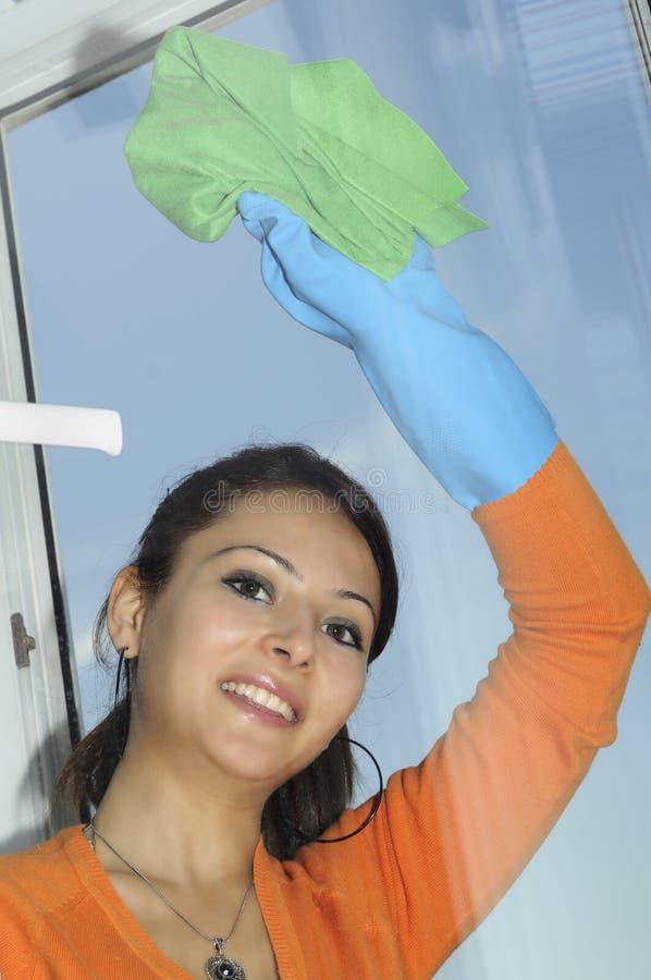 Mujer que limpia una ventana imágenes de archivo libres de regalías
