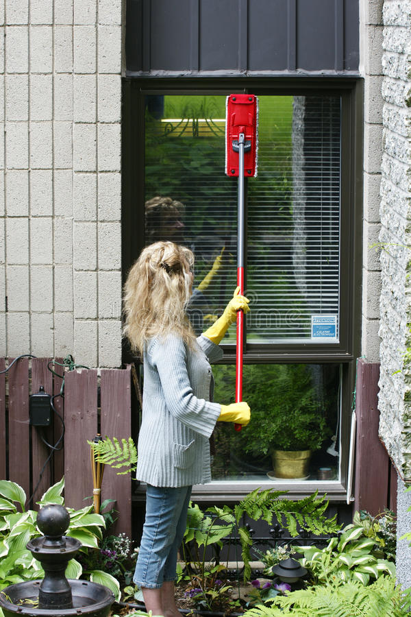 Mujer que limpia una ventana fotografía de archivo