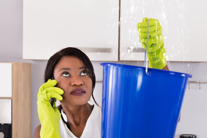 Mujer que llama al fontanero imagen de archivo