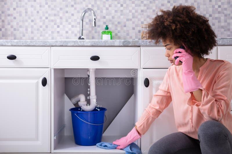 Mujer que llama el tubo de In Front Of Leaking From Sink del fontanero fotografía de archivo libre de regalías