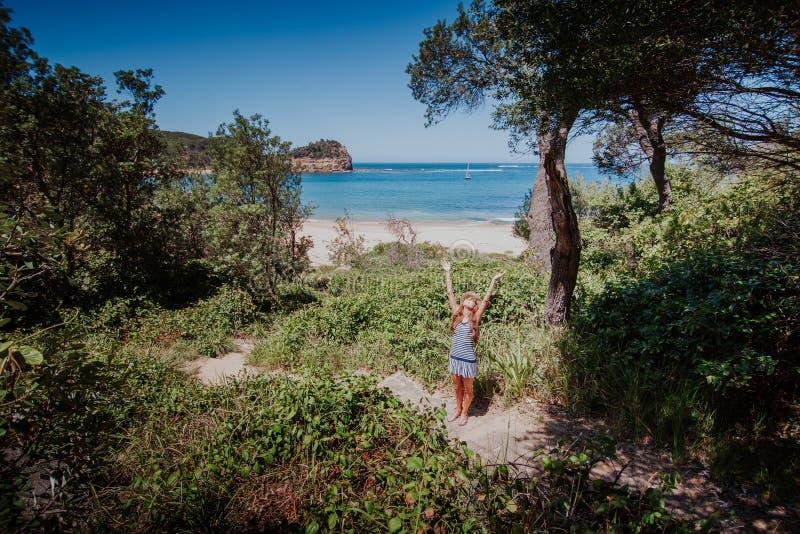 Mujer que llega a la playa después de caminar en el bosque imagenes de archivo