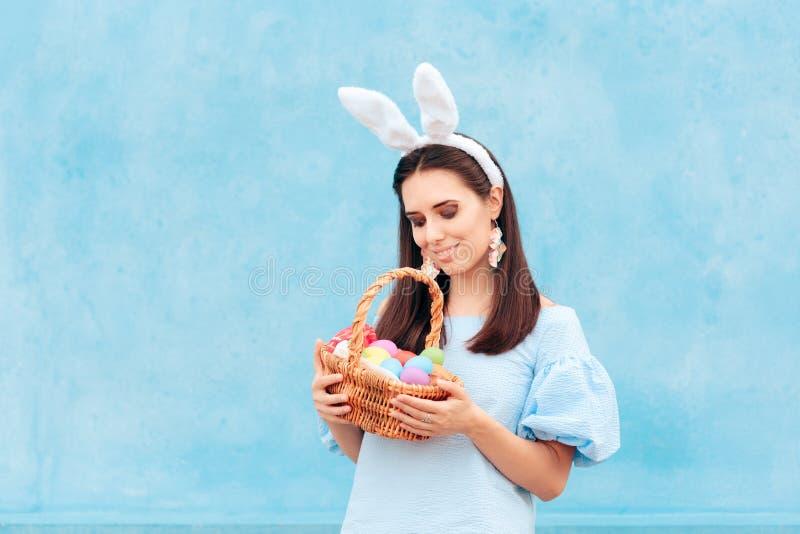 Mujer que lleva a Bunny Ears Holding Easter Basket de huevos imagenes de archivo