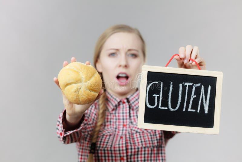 Mujer que lleva a cabo al tablero con la muestra del gluten y el pan del bollo fotografía de archivo libre de regalías