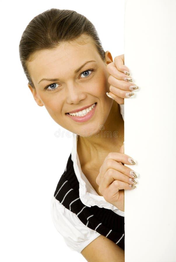 Mujer que lleva a cabo al tablero en blanco blanco imagen de archivo