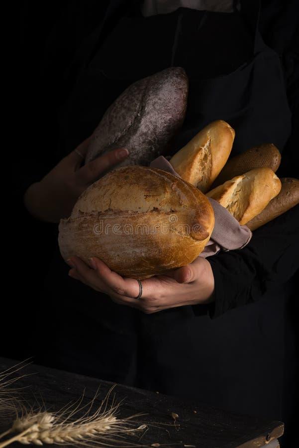 Mujer que lleva a cabo clases sabrosas del pan fresco en una oscuridad imagenes de archivo