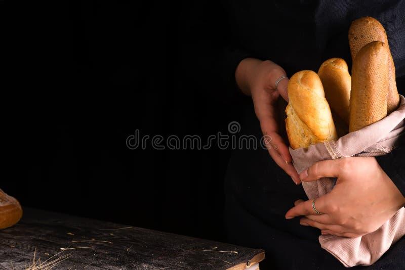 Mujer que lleva a cabo clases sabrosas del pan fresco en una oscuridad fotos de archivo libres de regalías