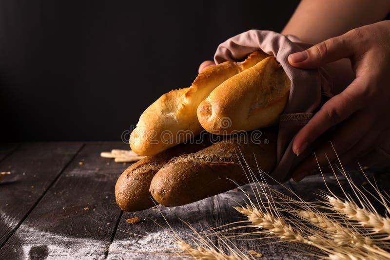 Mujer que lleva a cabo clases sabrosas del pan fresco en una oscuridad imagen de archivo