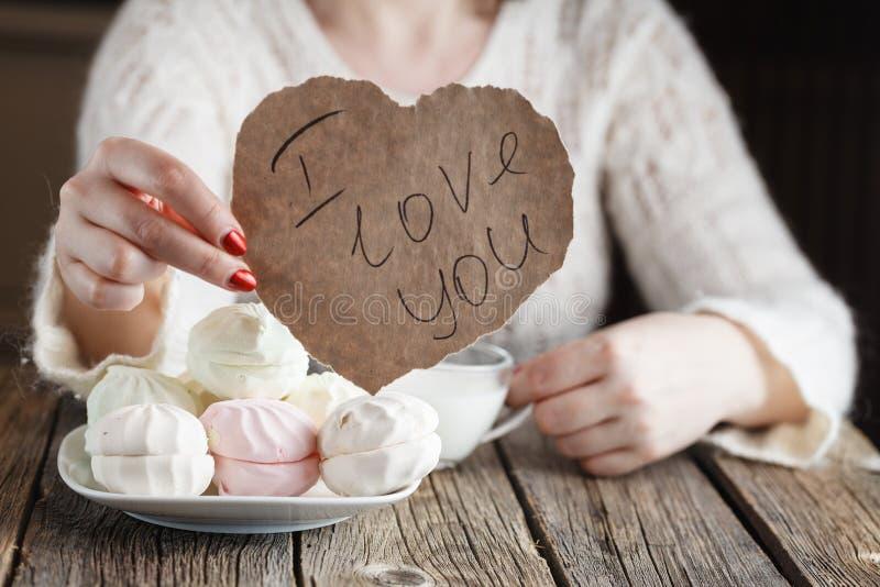 Mujer que lleva a cabo el corazón de papel mientras que come los dulces fotos de archivo libres de regalías
