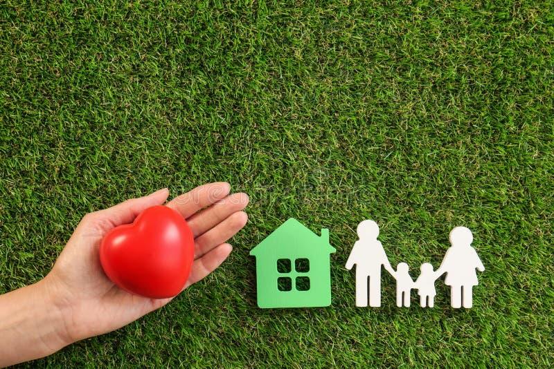 Mujer que lleva a cabo el corazón rojo a disposición cerca de figuras de y de la familia en la hierba verde, visión superior foto de archivo