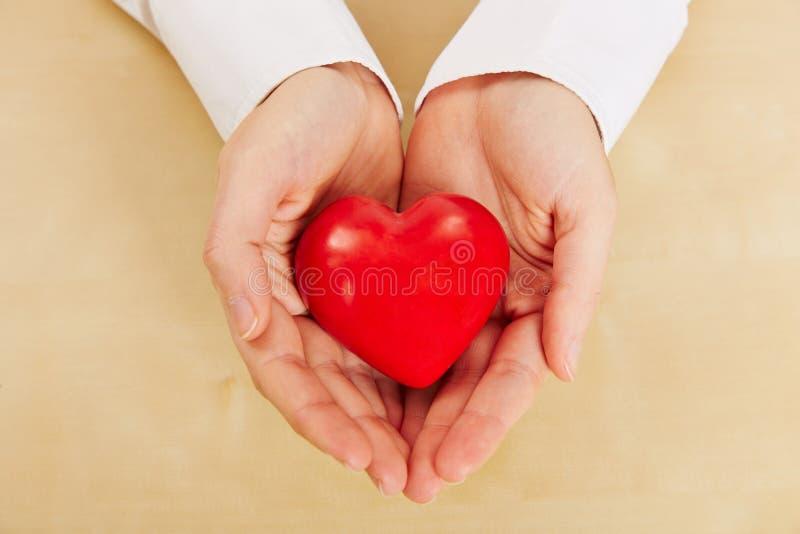 Mujer que lleva a cabo el corazón rojo en sus manos fotografía de archivo libre de regalías