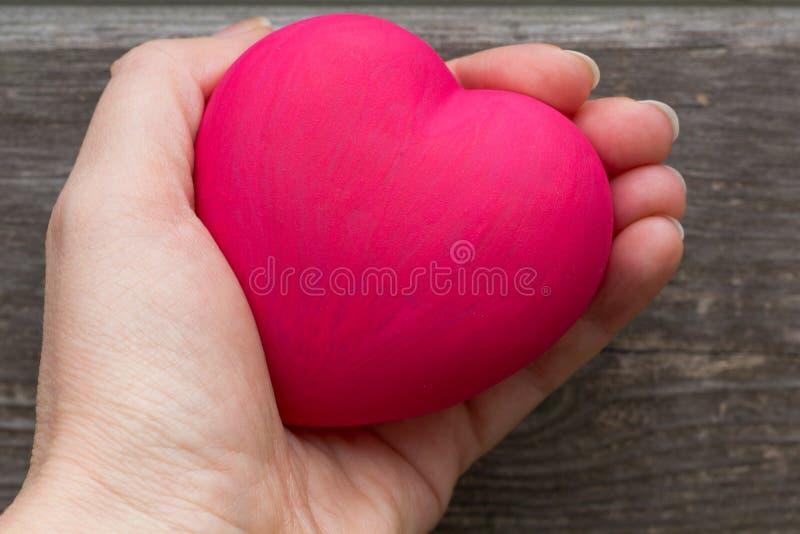 Mujer que lleva a cabo el coraz?n rojo en manos fotos de archivo libres de regalías