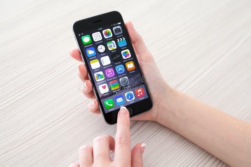 Mujer que lleva a cabo el espacio del iPhone 6 del teléfono gris sobre la tabla imagen de archivo libre de regalías