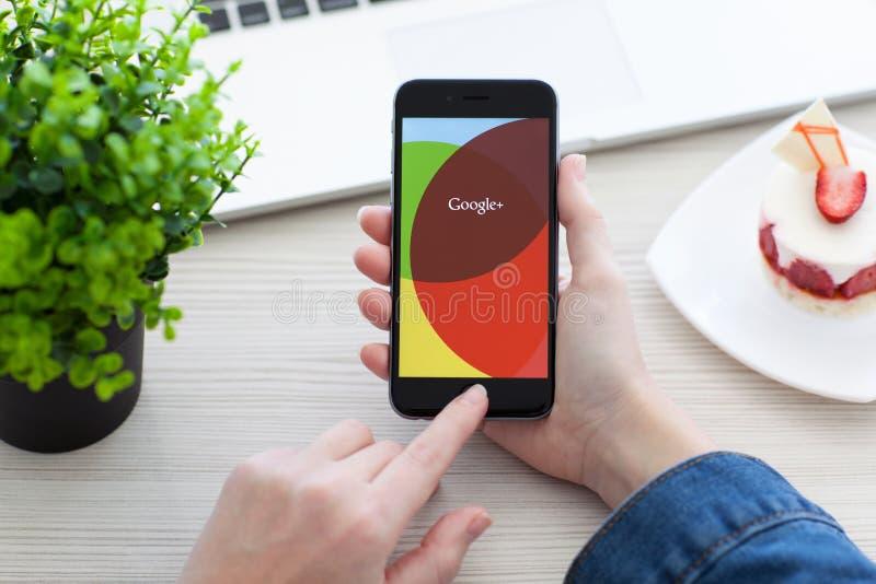 Mujer que lleva a cabo el espacio del iPhone 6 gris con el servicio Google+ imágenes de archivo libres de regalías