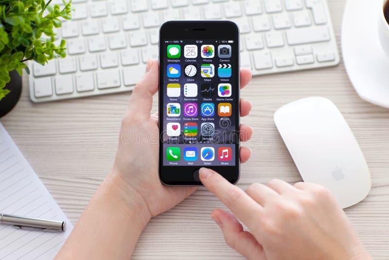 Mujer que lleva a cabo el espacio del iPhone 6 gris sobre la tabla fotografía de archivo