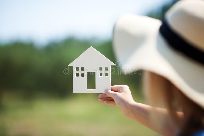 Mujer que lleva a cabo el modelo de la casa en el campo imagen de archivo