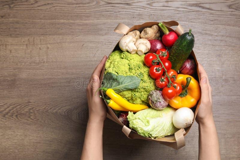 Mujer que lleva a cabo el paquete de papel por completo de verduras frescas imagen de archivo