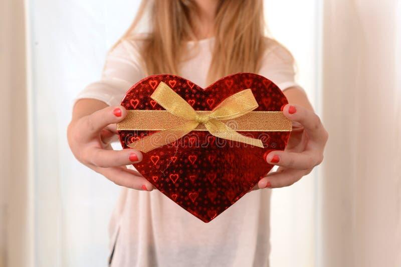 Mujer que lleva a cabo el presente en forma de corazón de la caja imagen de archivo