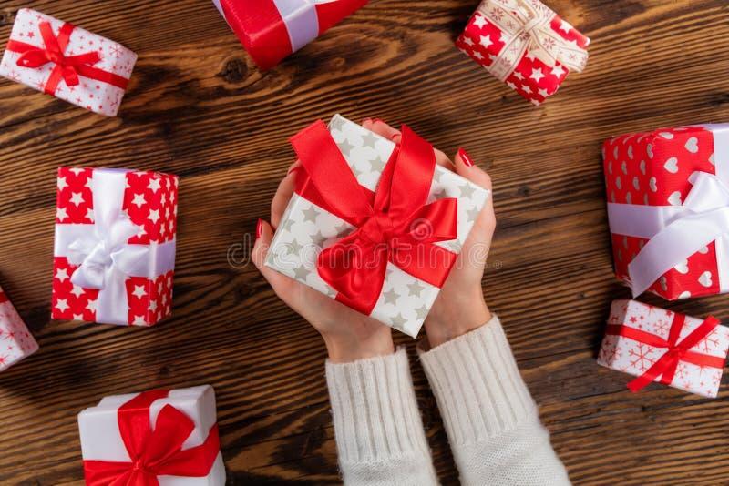Mujer que lleva a cabo el regalo de Navidad en fondo de madera de la tabla foto de archivo libre de regalías