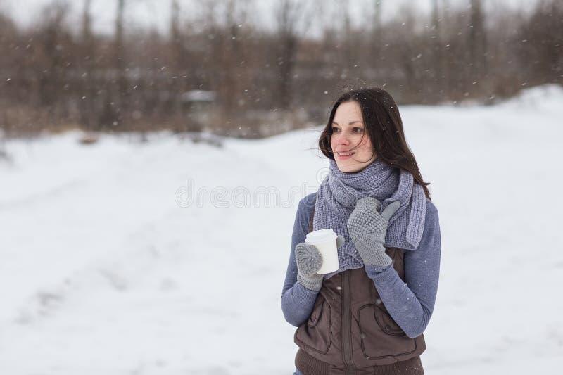 Mujer que lleva a cabo la bebida caliente afuera fotos de archivo