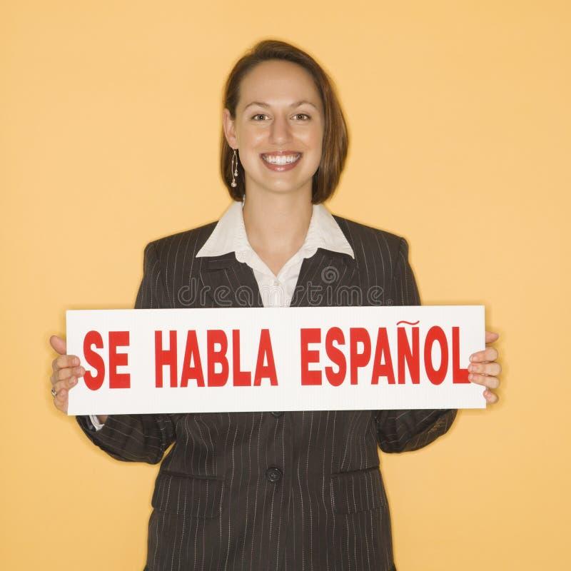 Mujer que lleva a cabo la muestra bilingüe foto de archivo libre de regalías