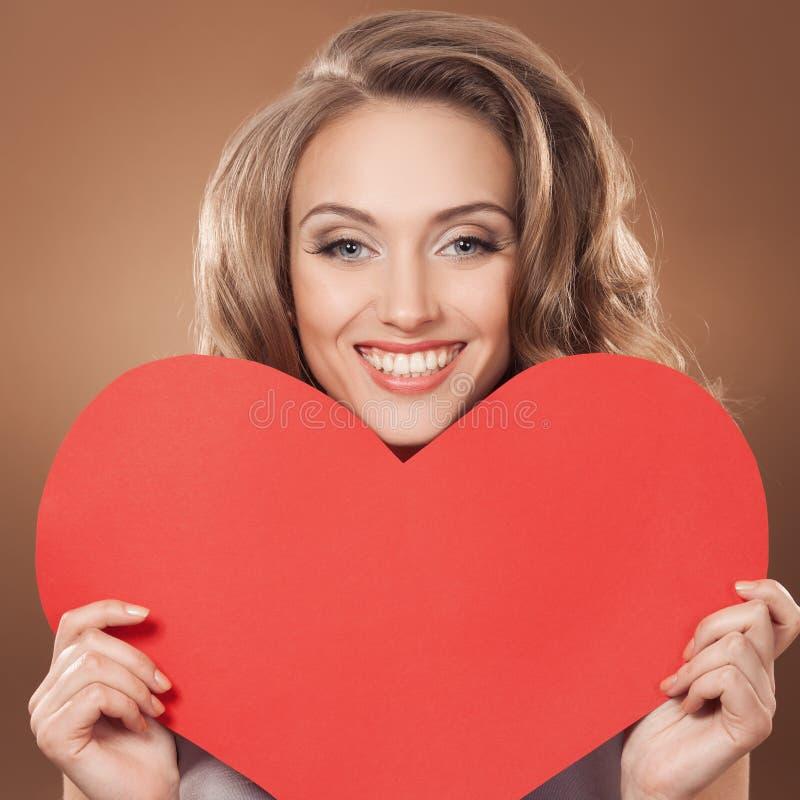 Mujer que lleva a cabo la muestra del corazón del día de tarjetas del día de San Valentín con el poli imagen de archivo