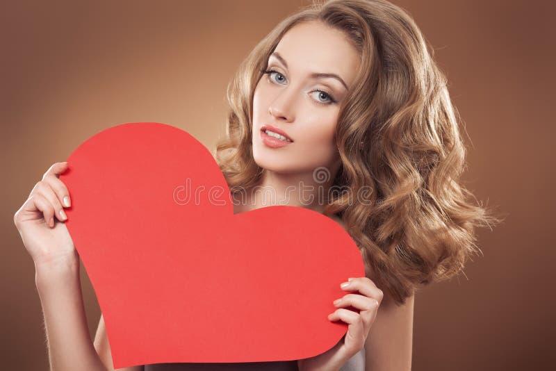 Mujer que lleva a cabo la muestra del corazón del día de tarjetas del día de San Valentín con el poli fotografía de archivo