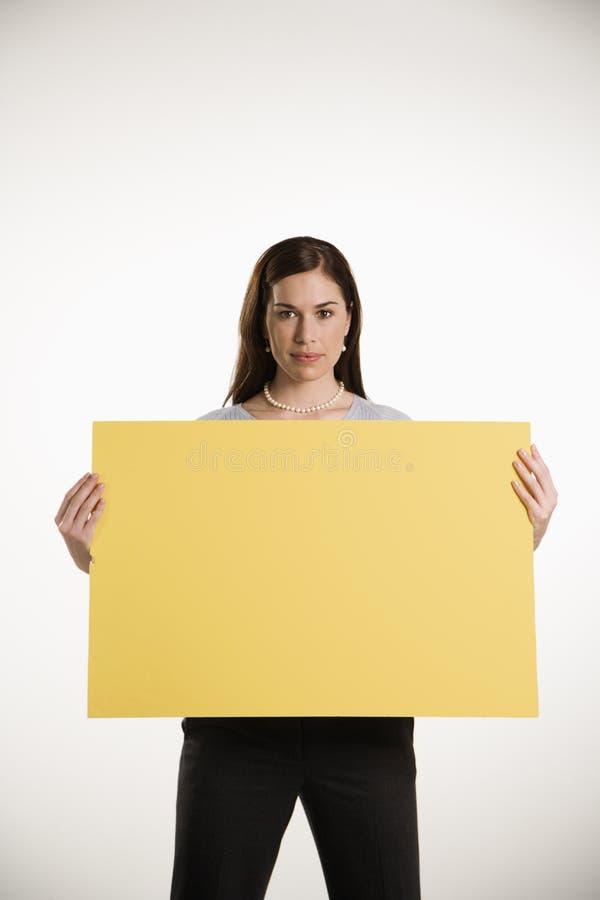 Mujer que lleva a cabo la muestra en blanco. fotografía de archivo libre de regalías