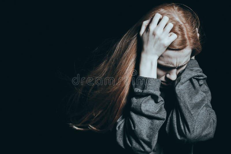 Mujer que lleva a cabo las manos en la cabeza imagenes de archivo