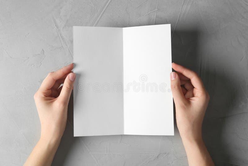 Mujer que lleva a cabo mofa en blanco del folleto para arriba en fondo ligero fotografía de archivo libre de regalías
