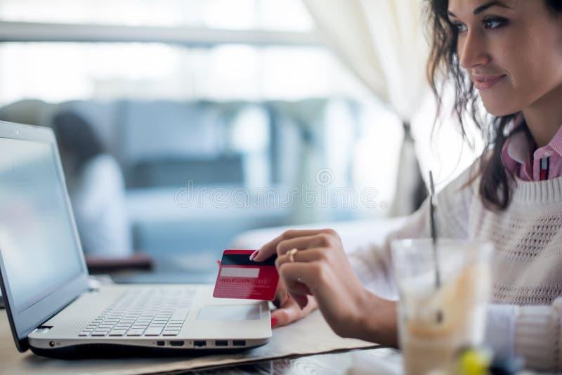 Mujer que lleva a cabo números que mecanografían de la tarjeta de crédito en el teclado de ordenador portátil Compras en línea imagen de archivo libre de regalías