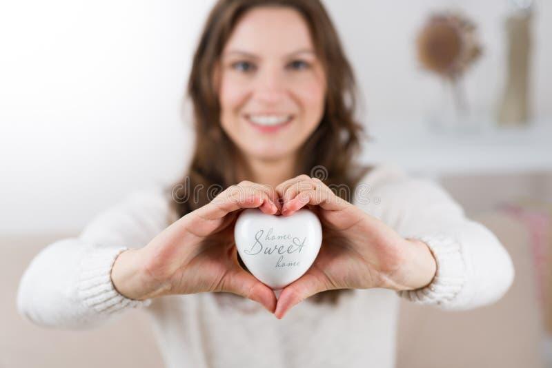 Mujer que lleva a cabo un corazón blanco - hogar dulce casero fotos de archivo