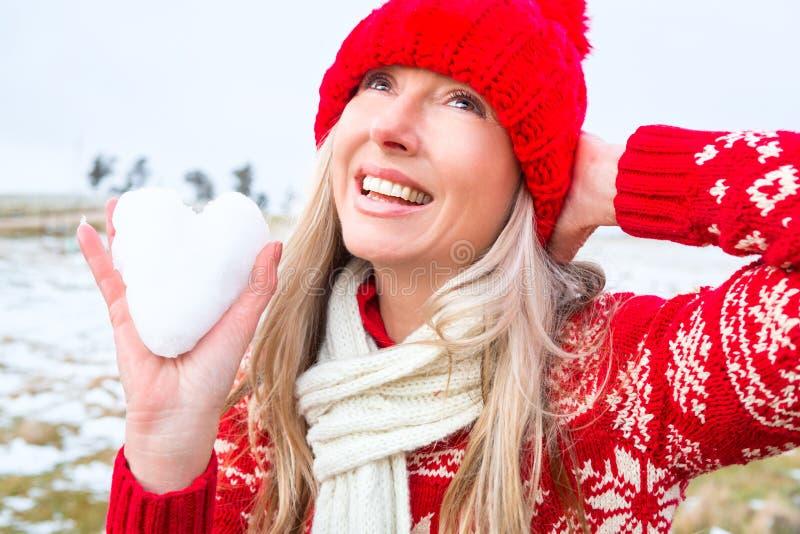 Mujer que lleva a cabo un corazón de la nieve Tema de la Navidad o del invierno imagen de archivo libre de regalías