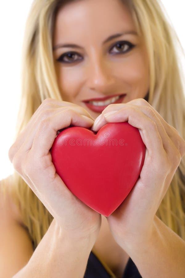 Mujer que lleva a cabo un corazón rojo imagen de archivo