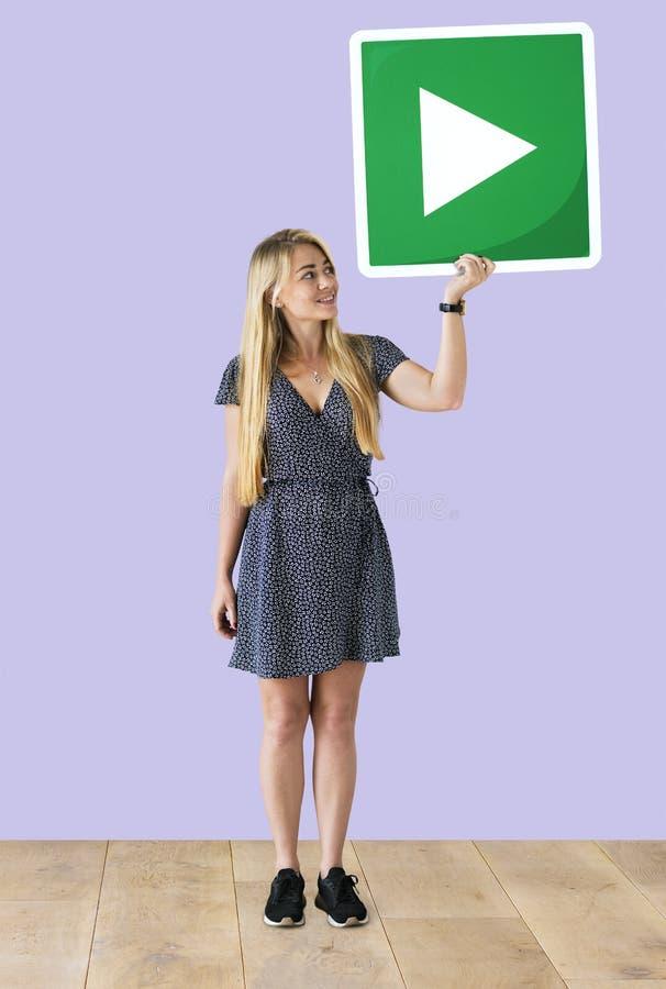 Mujer que lleva a cabo un icono del botón de reproducción en un estudio imagenes de archivo