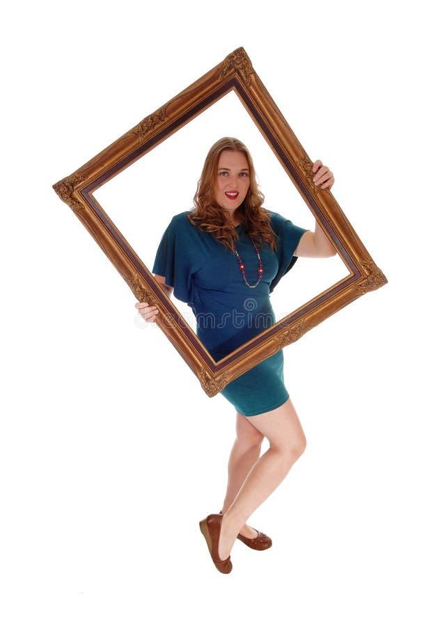 Mujer que lleva a cabo un marco fotos de archivo