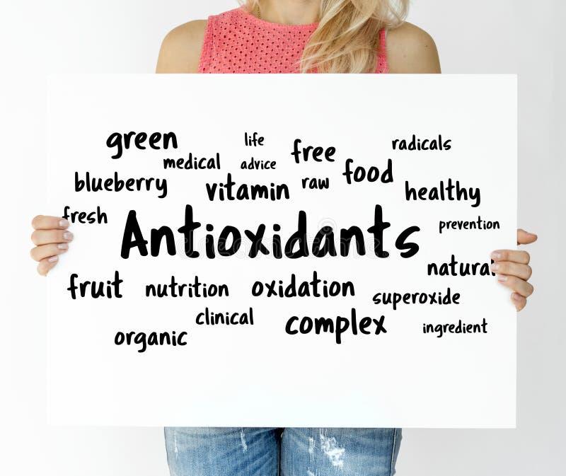 Mujer que lleva a cabo a un tablero con concepto de los antioxidantes imagen de archivo libre de regalías