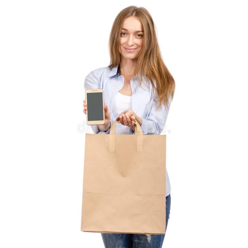Mujer que lleva a cabo una belleza de las compras del teléfono móvil del smartphone de la bolsa de papel foto de archivo libre de regalías