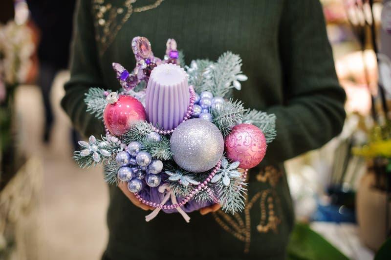 Mujer que lleva a cabo una composición linda n de la Navidad tonos rosados y azules hechos de vela, de árbol de abeto y de las bo foto de archivo libre de regalías
